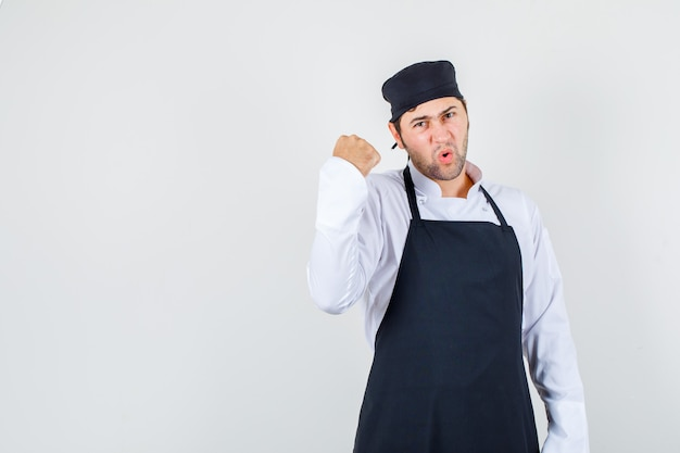 Mężczyzna szefa kuchni pokazujący zaciśniętą pięść w mundurze, fartuchu i wyglądający na oburzonego. przedni widok.