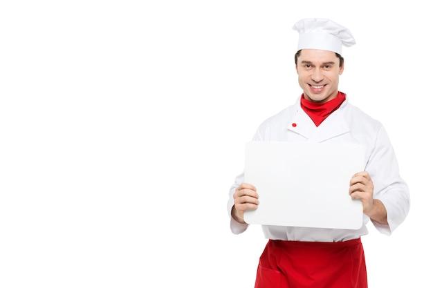 Mężczyzna szefa kuchni posiada tabliczkę znamionową menu na białym tle.