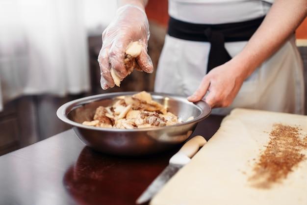 Mężczyzna szefa kuchni posyp ciasto cynamonem