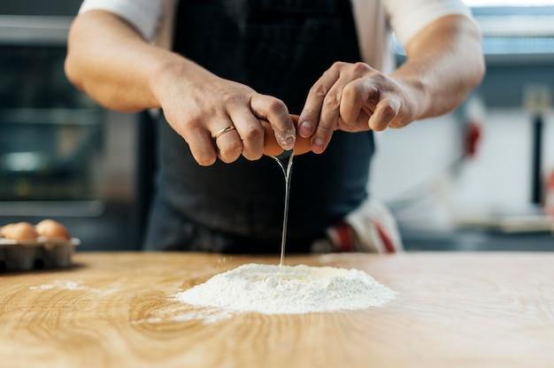 Mężczyzna szefa kuchni rozbija jajko na mąkę