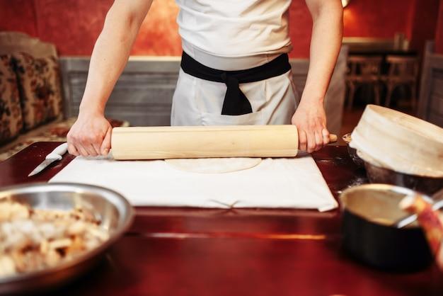 Mężczyzna szefa kuchni rozwałkowuje ciasto wałkiem do ciasta