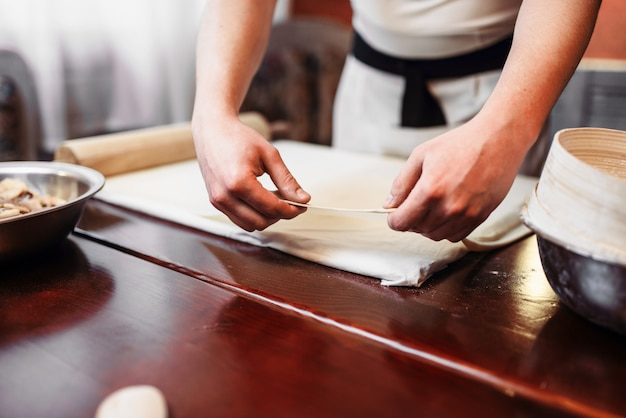 Mężczyzna szefa kuchni strudel jabłkowy gotowania w kuchni. domowy słodki deser, proces przygotowania