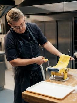 Mężczyzna szefa kuchni toczenia ciasta makaronowego w kuchni