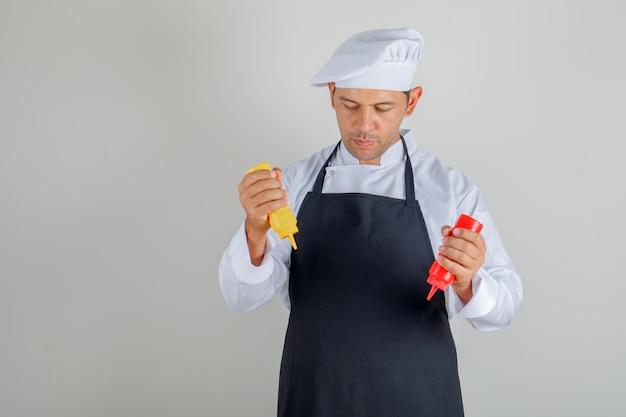 Mężczyzna szefa kuchni trzymając butelki keczupu i musztardy w kapeluszu, fartuchu i mundurze