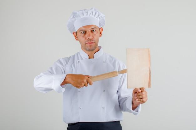 Mężczyzna szefa kuchni trzymając deskę do krojenia i wałek do ciasta w mundurze, fartuch i kapelusz