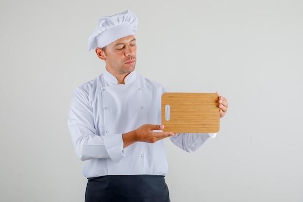 Mężczyzna szefa kuchni trzymając deskę do krojenia w mundurze, fartuch i kapelusz