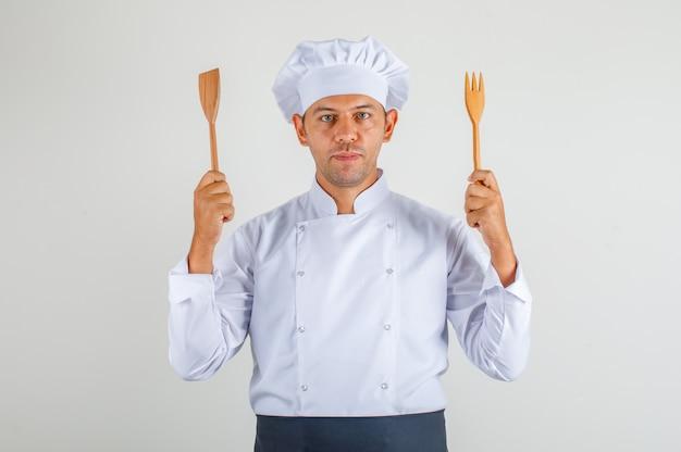 Mężczyzna szefa kuchni trzymając drewniane naczynia kuchenne w mundurze, fartuch i kapelusz