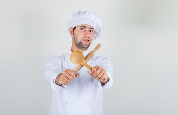 Mężczyzna szefa kuchni w białym mundurze, trzymając drewnianą łyżkę i wałkiem do ciasta