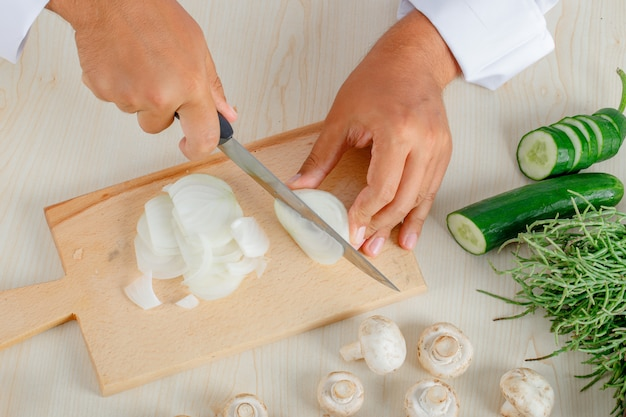 Mężczyzna szefa kuchni w mundurze do krojenia cebuli na deskę do krojenia w kuchni