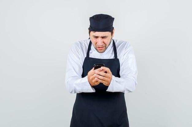 Mężczyzna szefa kuchni w mundurze, fartuch przy użyciu smartfona i wyglądający na zdziwionego, widok z przodu.