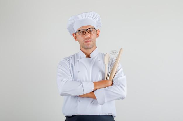 Mężczyzna szefa kuchni w mundurze, fartuchu i kapeluszu, trzymając naczynia kuchenne ze skrzyżowanymi rękami i patrząc ostrożnie