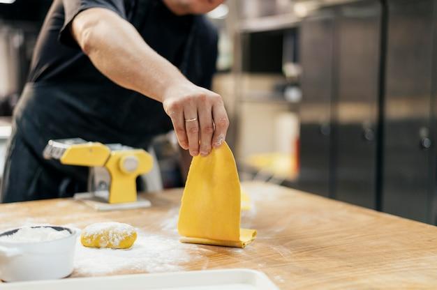Mężczyzna szefa kuchni z fartuch i świeże ciasto makaronowe