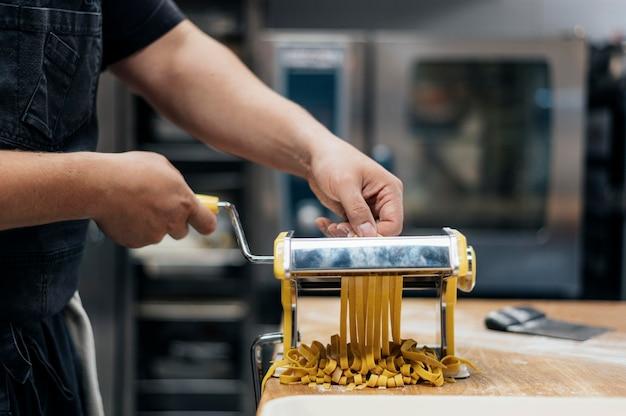 Mężczyzna szefa kuchni za pomocą maszyny do siekania świeżego ciasta makaronowego