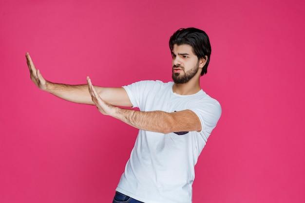 Mężczyzna szeroko otwierając ręce i próbując coś zatrzymać.