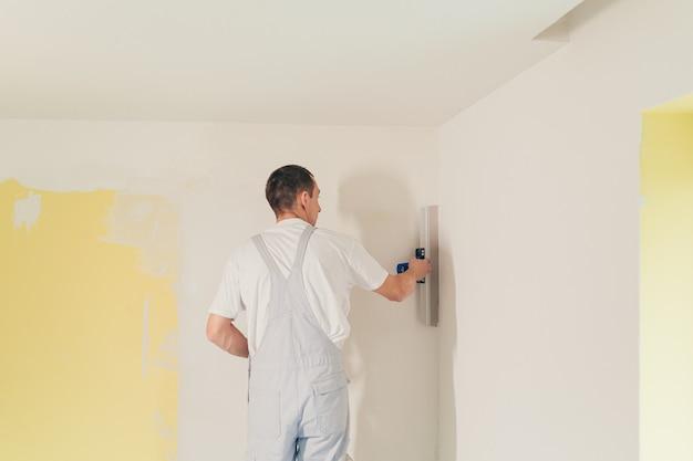 Mężczyzna szpachluje ściany w mieszkaniu szpachelką robi naprawy
