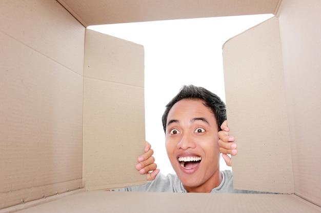 Mężczyzna szuka czegoś wewnątrz pudełka