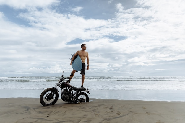 Mężczyzna szuka inspiracji stojąc na motocyklu sportowym. trzymając w rękach deskę surfingową. młody człowiek surfer korzystających z rekreacji w pobliżu oceanu.