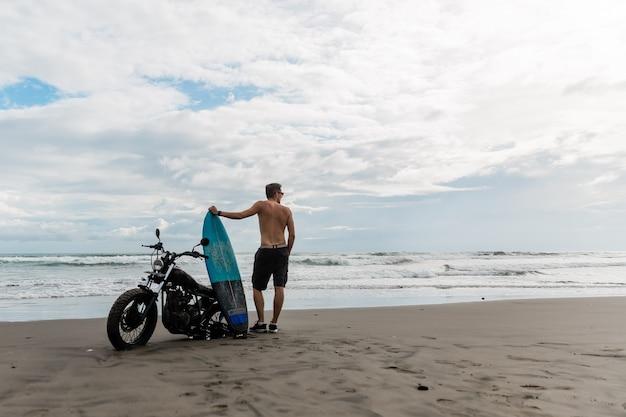 Mężczyzna szuka inspiracji, stojąc w pobliżu sportowego motocykla. trzymając w rękach deskę surfingową. młody człowiek surfer korzystających z rekreacji w pobliżu oceanu.