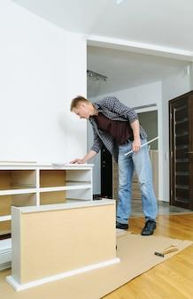 Mężczyzna szuka instrukcji montażu mebli