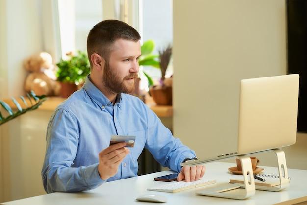 Mężczyzna szuka produktów do kupienia w sklepie internetowym na swoim laptopie z kartą kredytową w domu