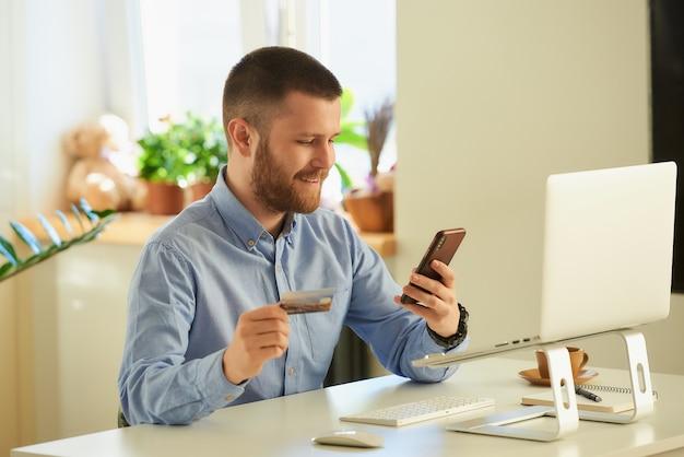 Mężczyzna szuka produktów do kupienia w sklepie internetowym na swoim smartfonie za pomocą karty kredytowej w domu