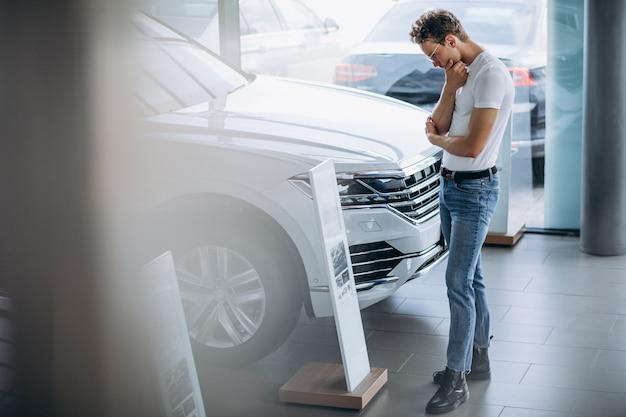 Mężczyzna szuka samochodu w salonie samochodowym