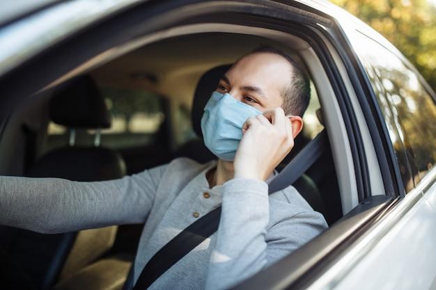 Mężczyzna taksówkarz prowadzi samochód i dopasowuje maskę medyczną podczas wybuchu koronawirusa.