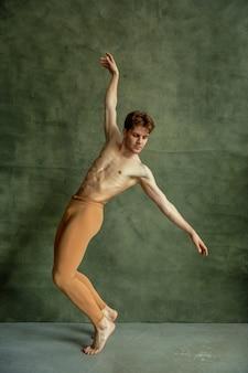 Mężczyzna tancerz baletu pozuje na ścianie grunge w studio tańca. wykonawca o muskularnym ciele, wdzięku i elegancji tańca