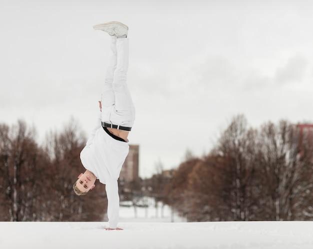 Mężczyzna tancerz równoważenia ciała z jednej strony na zewnątrz