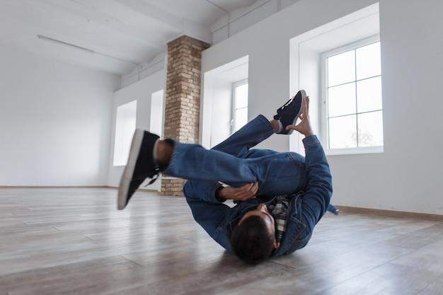 Mężczyzna tancerz w dżinsowych ubraniach mody, taniec w studio