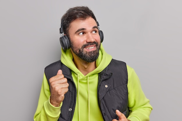 Mężczyzna tańczy beztroskie ruchy w rytm ulubionej muzyki odwraca wzrok nosi bezprzewodowe słuchawki na uszach nosi swobodną bluzę z kapturem i kamizelkę odizolowane na szaro