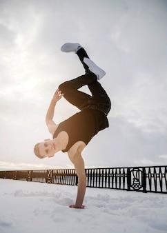 Mężczyzna tańczy do hip-hopu, stojąc w jednej ręce w śniegu