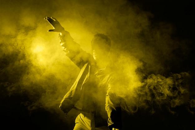 Mężczyzna tańczy w dymie z oświetlającym światłem