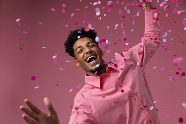 Mężczyzna tańczy z konfetti średni strzał