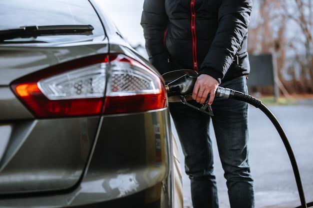 Mężczyzna tankuje samochód na stacji benzynowej, zatankuj samochód