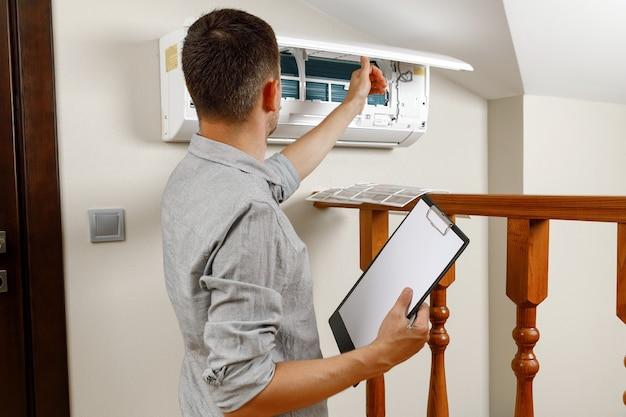 Mężczyzna technik czyszczenia klimatyzatora w pomieszczeniu. mężczyzna z tabletem w dłoniach