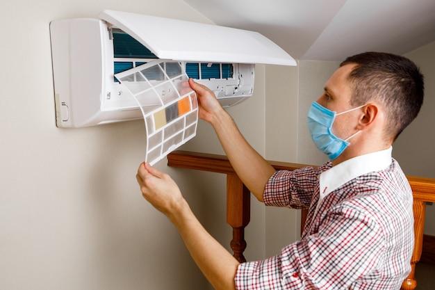 Mężczyzna technik czyszczenia klimatyzatora w pomieszczeniu