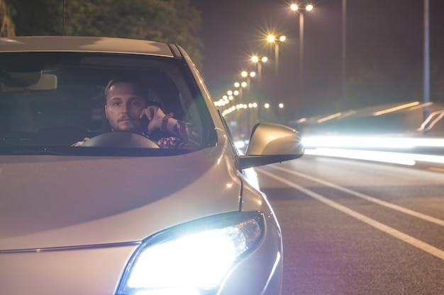 Mężczyzna telefon w samochodzie na drodze. wieczorna pora nocna