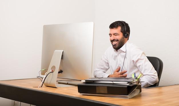 Mężczyzna telemarketer w biurze uśmiechając się dużo, kładąc ręce na klatce piersiowej