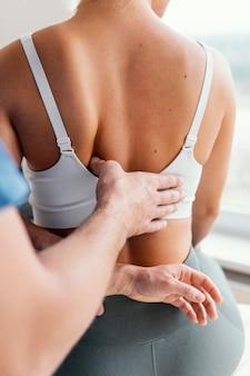 Mężczyzna terapeuta osteopatyczny sprawdza ból pleców pacjentki