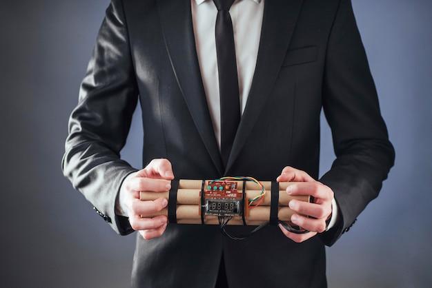 Mężczyzna terrorysta w czarnym garniturze z materiałami wybuchowymi