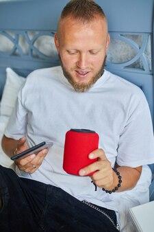 Mężczyzna testujący mówiący inteligentny głośnik bezprzewodowy, mężczyzna kontrolujący urządzenia domowe za pomocą poleceń głosowych, siedzący na kanapie w domu, koncepcja inteligentnego domu