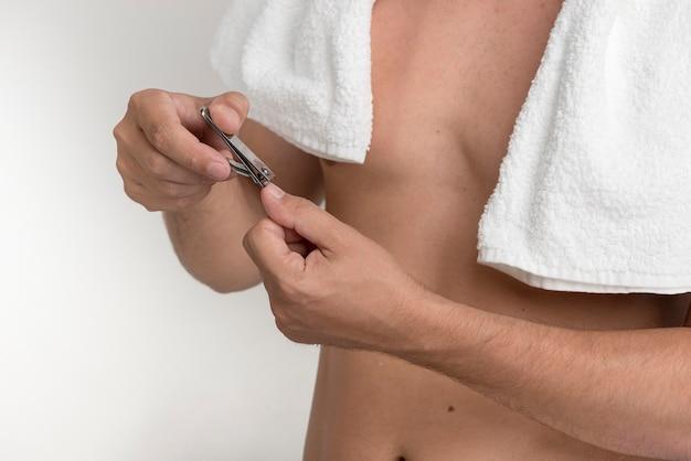 Mężczyzna tnący palcowi gwoździe z gwoździa cążkiem przeciw białemu tłu