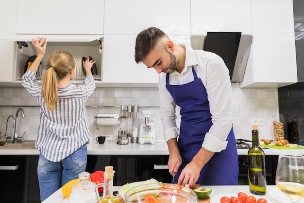 Mężczyzna tnący warzywa podczas gdy kobieta bierze talerze