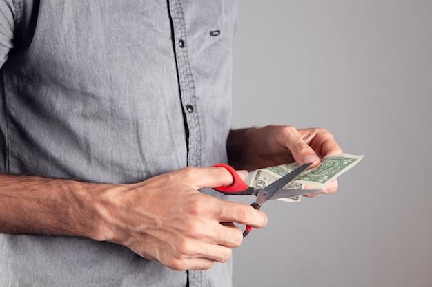 Mężczyzna tnie banknot dolarowy nożyczkami