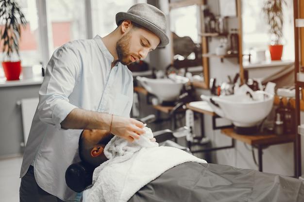 Mężczyzna tnie brodę w salonie fryzjerskim.