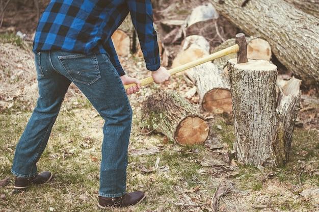 Mężczyzna tnie drewno siekierą w ciągu dnia