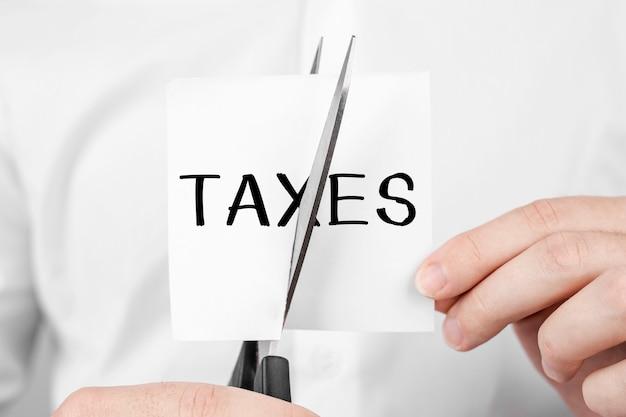 Mężczyzna tnie naklejkę nożyczkami z tekstem podatki