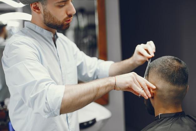 Mężczyzna tnie włosy w zakładzie fryzjerskim