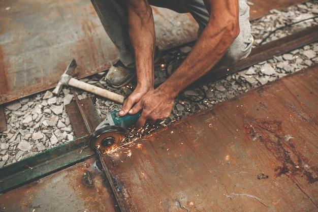 Mężczyzna tnie żelazo na ulicy.